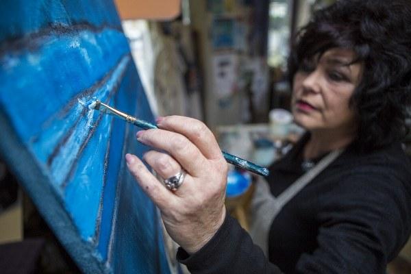 Beeldend kunstenaar Sia-Braakman geconcentreerd aan het schilderen in haar atelier
